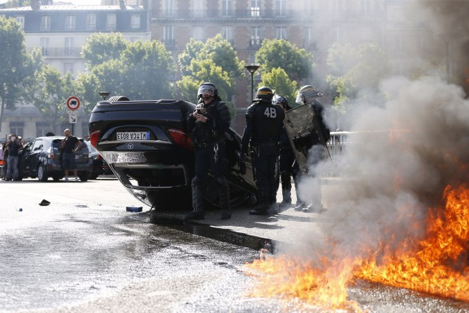 Smoke rises from a fire burning next to French CRS riot police standing near an overturned car as taxi drivers block Porte Maillot in Paris on June 25, 2015. Hundreds of taxi drivers converged on airports and other areas around the capital to demonstrate against UberPOP, a popular taxi app that is facing fierce opposition from traditional cabs. Access to three terminals at Paris-Charles de Gaulle airport and in a number of areas of Paris, especially Porte Maillot, were blocked. AFP PHOTO / THOMAS SAMSON (Photo credit should read THOMAS SAMSON/AFP/Getty Images)