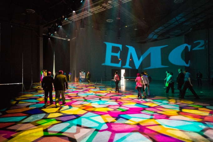 EMC logo over psychedelic dance floor
