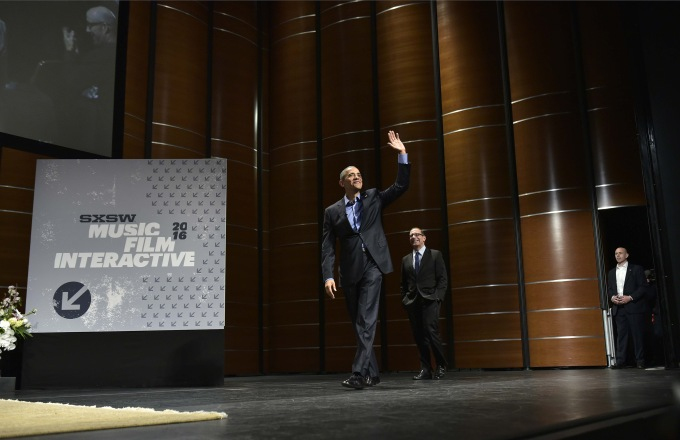 US President Barack Obama waves as he and Texas Tribune editor Evan Smith (C) arrive for a South by Southwest Interactive at the Long Center for Performing Arts in Austin, Texas on March 11, 2016. / AFP / MANDEL NGAN
