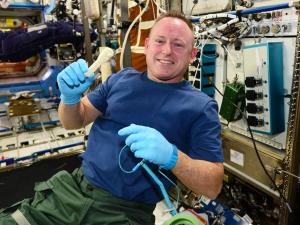 Astronaut Barry Wilmore with a 3D printed ratchet / Image courtesy of NASA