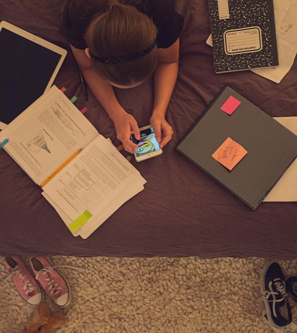 girl-doing-homework-on-bed