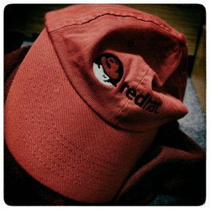 Crumpled cap with Red Hat logo on it.