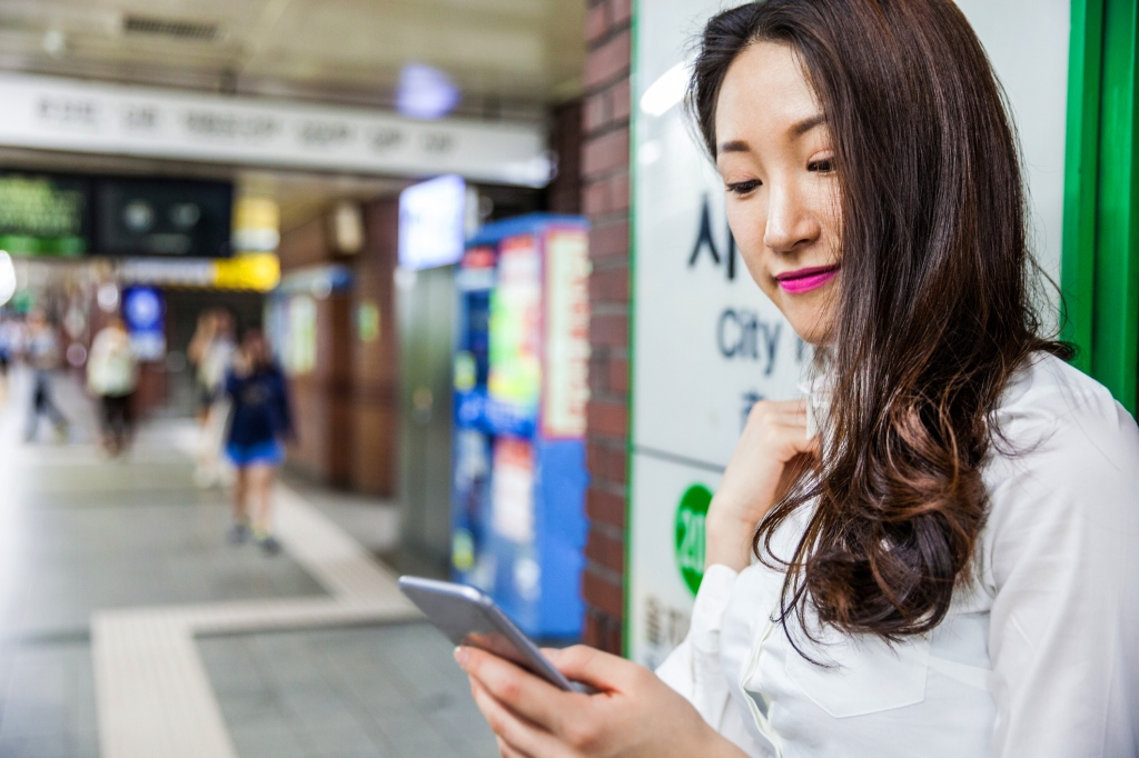 Smiling young business woman in subway station, South Korea. (Leonardo Patrizi/Getty Images)