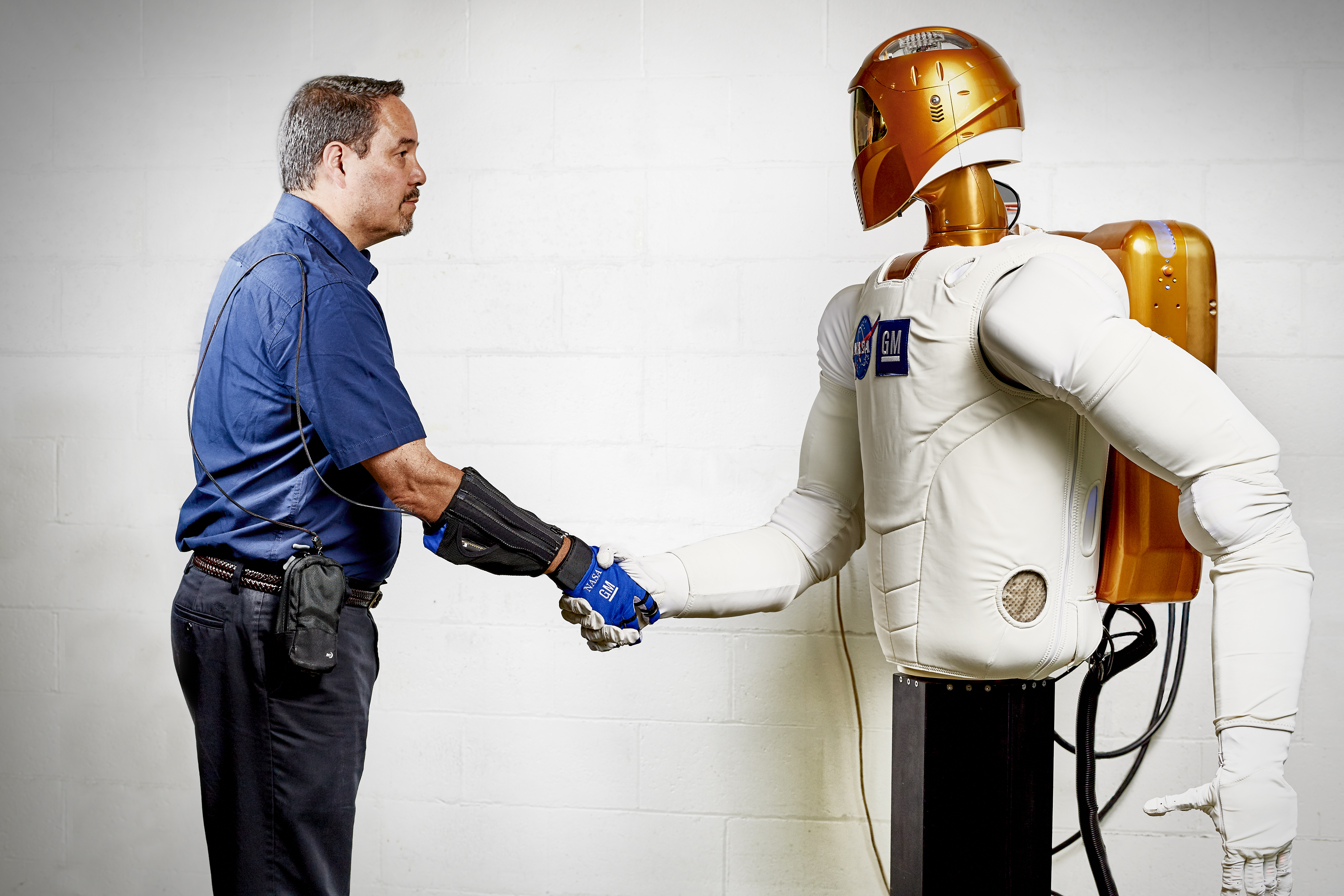 Marty Linn, General Motors manager of advanced technology and principal engineer for robotics, shakes hands with Robonaut 2 (R2), a humanoid robot developed by GM and NASA during a nine-year collaboration that also led to development of the RoboGlove, an exo-muscular device that enhances strength and grip through leading-edge sensors, actuators and tendons that are comparable to the nerves, muscles and tendons in a human hand. GM is licensing the RoboGlove intellectual property to Bioservo Technologies AB, a Swedish medical technologies company that will combine RoboGlove with its owner patented SEM glove technology.