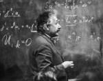erman-born physicist Albert Einstein (1879 - 1955) standing beside a blackboard with chalk-marked mathematical calculations written across it.
