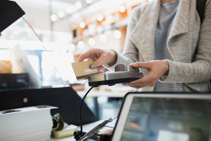 customer paying at credit card reader in market - Prepaid Card With Overdraft Protection