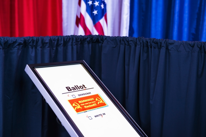 Russians hacked electronic voting machine, showing a red warning window withhammer and sickle icon at a polling station decorated in red, white and blue with an American flag in the background. This is a new form of cyber warfare.