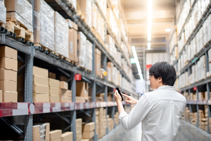 Young Asian man checking the shopping list on his smartphone in warehouse