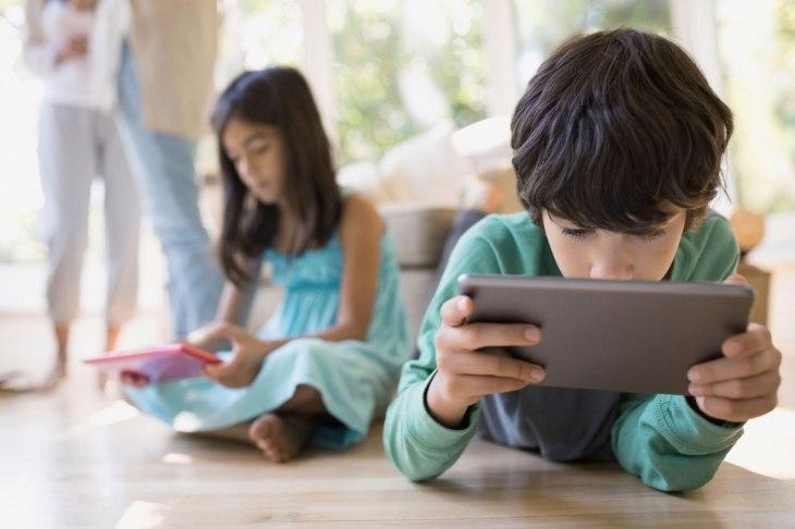 Boy using digital tablet on living room floor