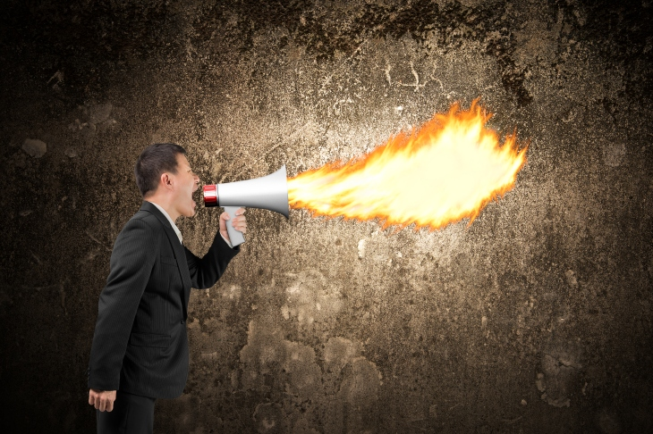 Angry businessman screaming into megaphone spitting fire illumin