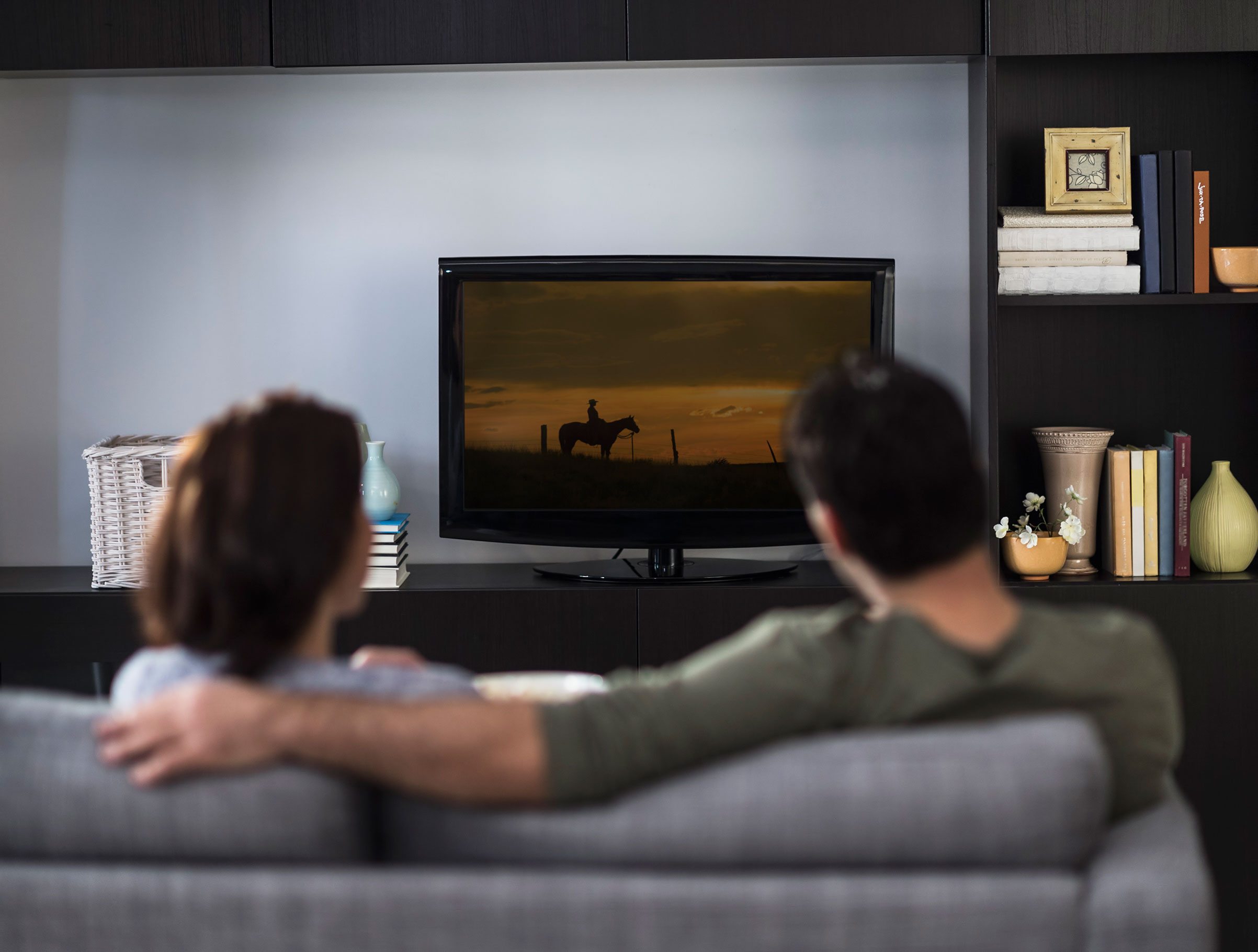 Couple watching TV on their couch.