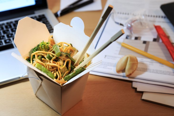 Chinese food box on the office desk. Eating at the office. Overtime work concept.