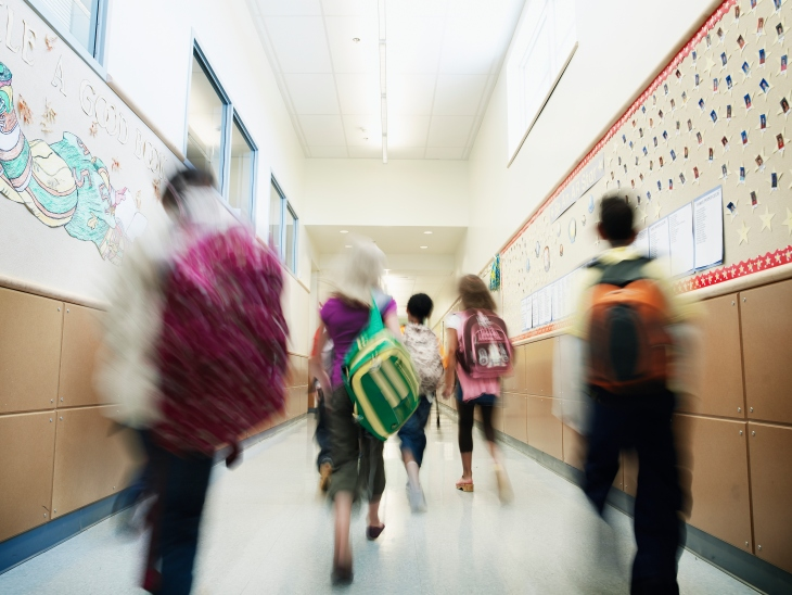 Young students walking down hallway of school
