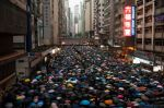 Protesters march while holding umbrellas during the