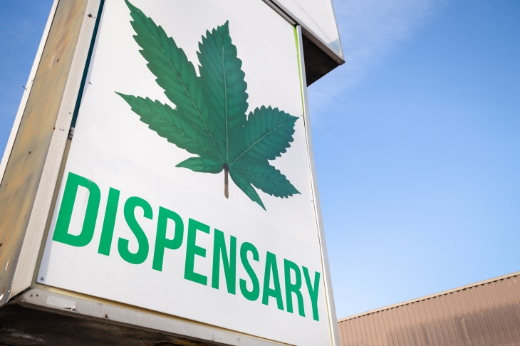 A cannabis dispensary sign with a large marijuana leaf on it.