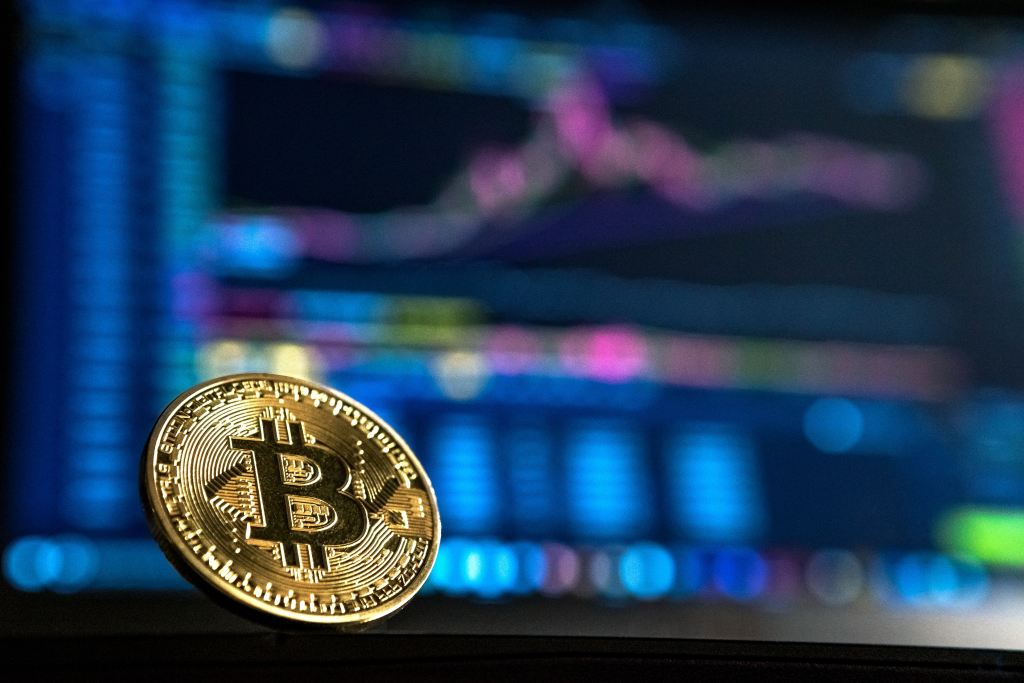 A bitcoin token in front of charts
