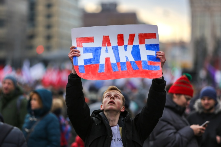 A protester seen holding a placard saying fake during the