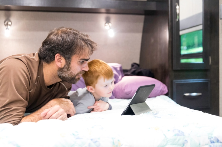 Father and Son Watching a Television Show on Digital Tablet in Camper Trailer