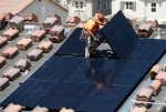Workers install solar panels on the roofs of homes under construction in California.