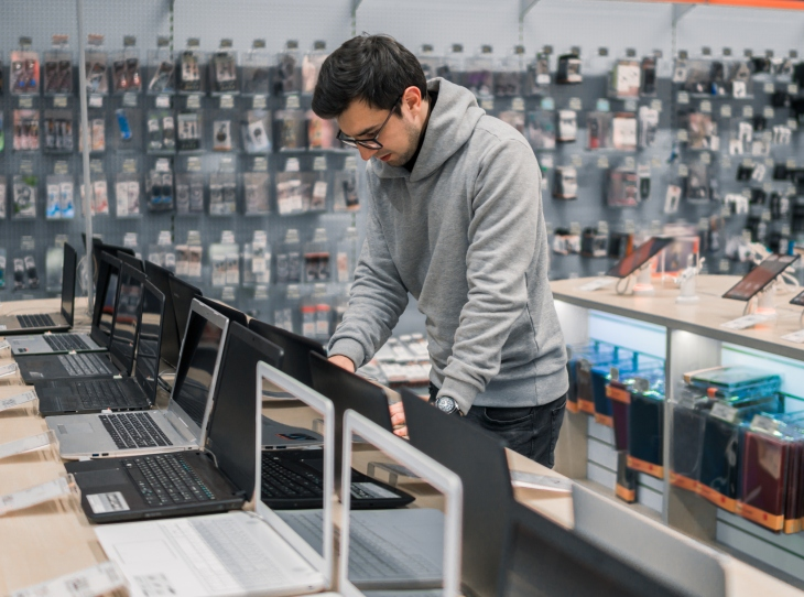modern male customer choosing laptop in the computer shop