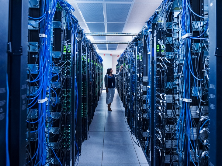 Woman standing in aisle of server room