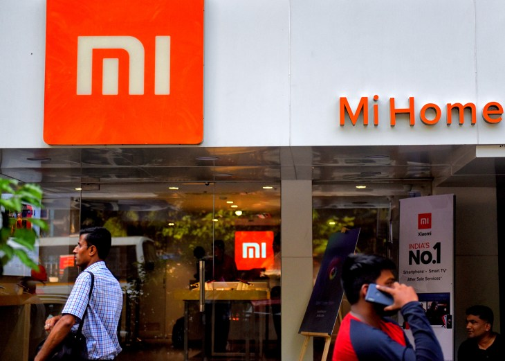 People are seen walking past an MI home mobile store in