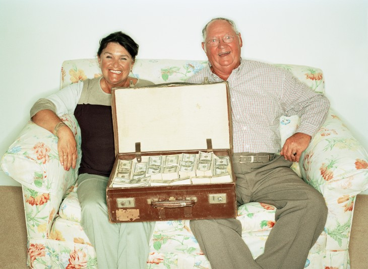 Mature couple on sofa with suitcase full of money