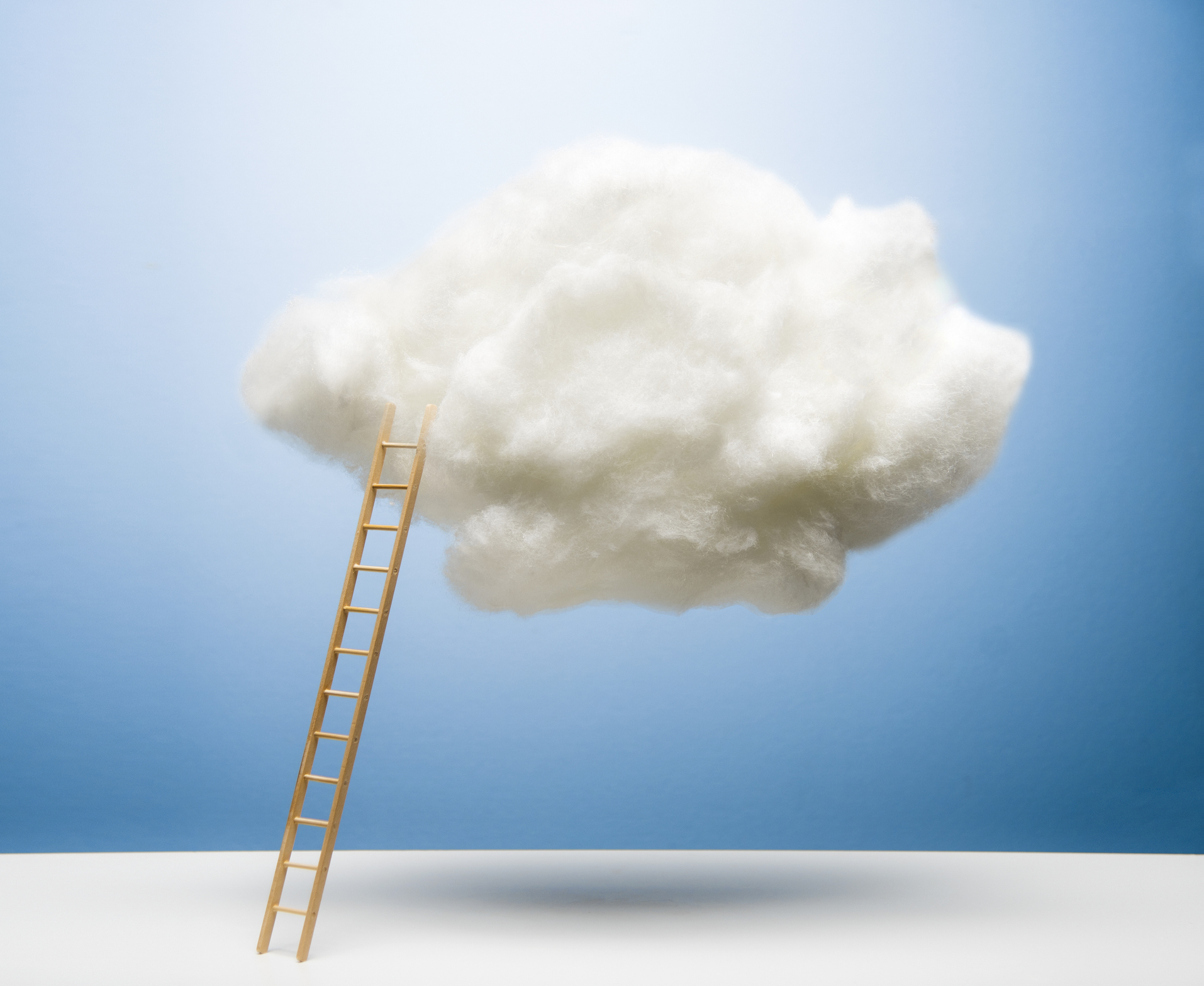 Ladder leaning on white puffy cloud on blue studio background, white surface, drop shadow