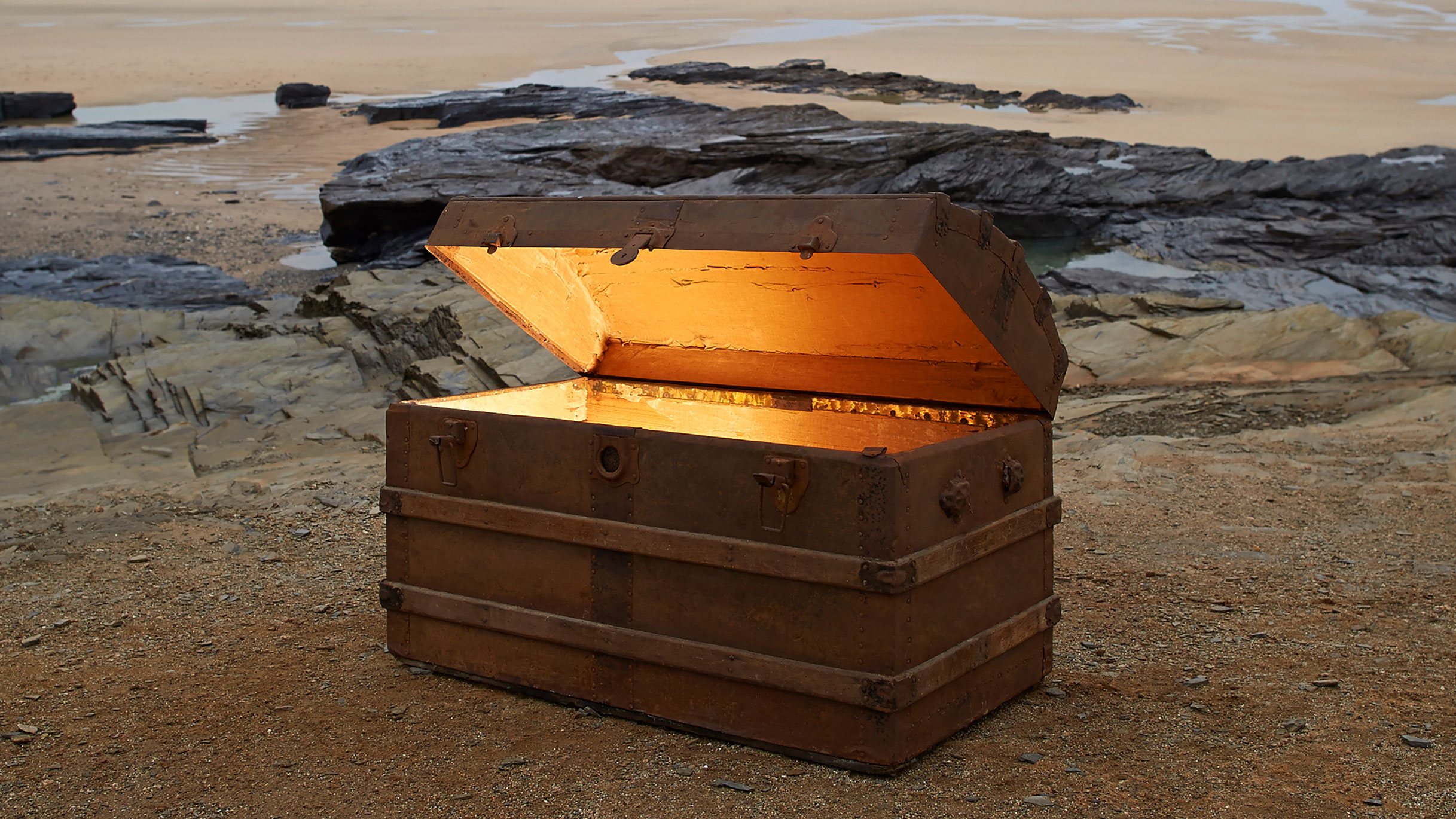 Open treasure chest of gold on a deserted beach.