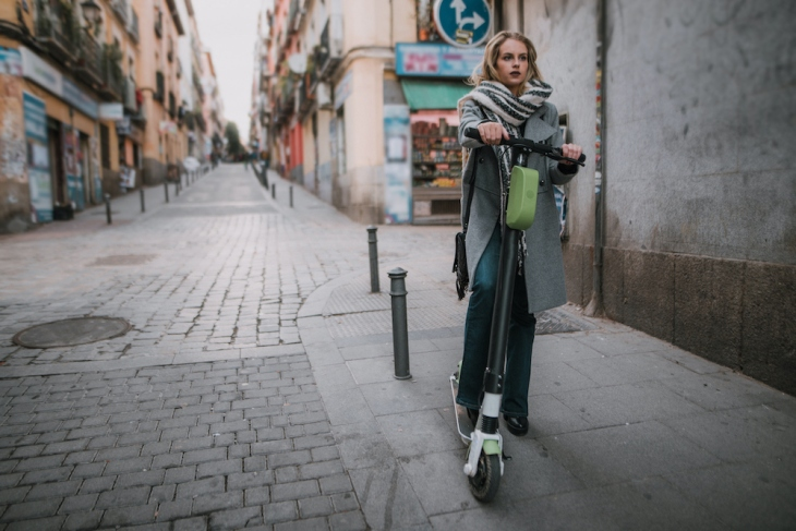 Young woman riding an electric scooter in a city