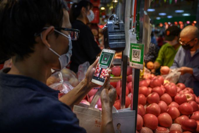 BEIJING, CHINA - SEPTEMBER 19: A Chinese customer uses his mobile to pay via a QR code with the WeChat app at a local market on September 19, 2020 in Beijing, China. (Photo by Kevin Frayer/Getty Images)