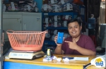 An image of an Indonesian merchant holding a smartphone with BukuWarung's app