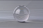 Crystal Ball Refraction Illusion on Black and White Striped Pattern.