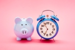 Retro alarm clock and blue piggy bank on pink background