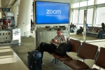 San Jose, CA, USA - Feb 13, 2020: A businessman checks his smartphone in San Jose International Airport with Zoom Video Communications advertisement on the screen in the background. Zoom provides remote conferencing services using cloud computing and has quickly emerged as one of the leading tools to keep business running and student learning.