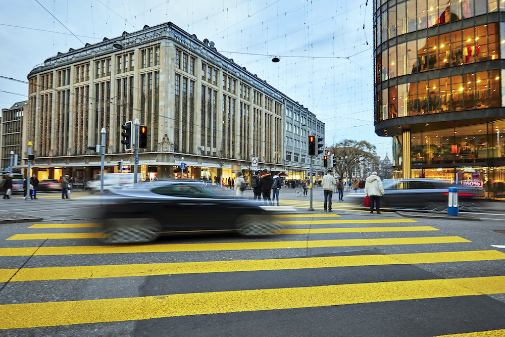 Busy Zurich street scene with blurred electric car and pedestrians. Luxury electric cars are popular in Zurich. In the background are retail shops and offices. Zürich often ranks in the top ten most liveable cities in the world.