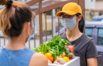A grocery store delivery person wearing an orange cap and face mask. She is delivering groceries to a woman.