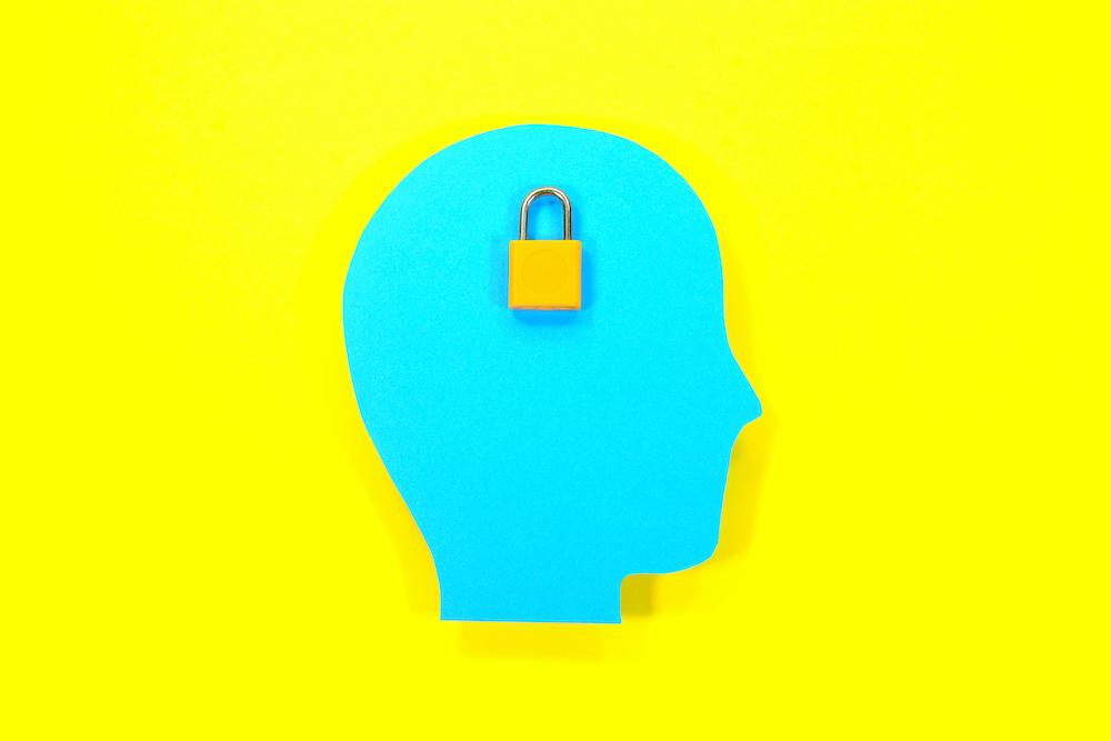 Konsep pengetahuan, data dan perlindungan. Kertas kepala manusia dengan kunci bantalan.