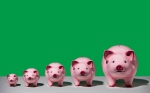 Line of differently sized pink ceramic piggy banks in ascending size order on white surface, green background