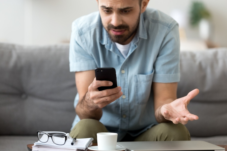 Close up confused man having problem with phone, receive bad news