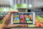 Woman holding a mobile phone using an augmented reality application to check special sale prices of fruits in a grocery. (Woman holding a mobile phone using an augmented reality application to check special sale prices of fruits in a grocery., ASCII,