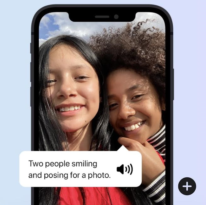 A phone showing a photo of two women smiling and voiceover describing the photo