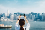Woman taking photo of Hong Kong skyline with a smartphone