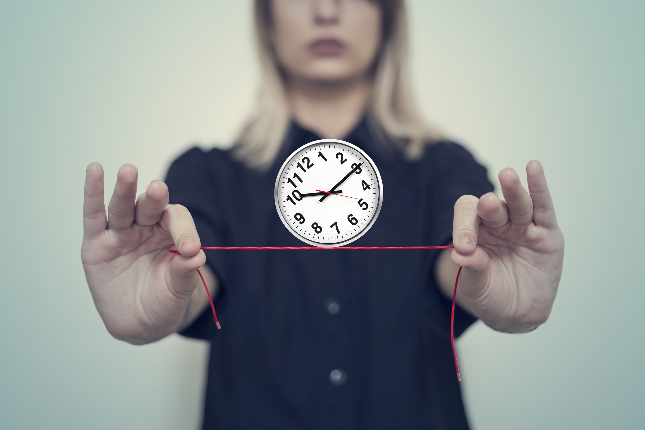 A woman's hand holds a balanced wall clock on a string