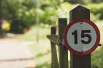 Close-Up Of Speed LimSign On Wooden Fence, photo taken In Epsom, United Kingdom