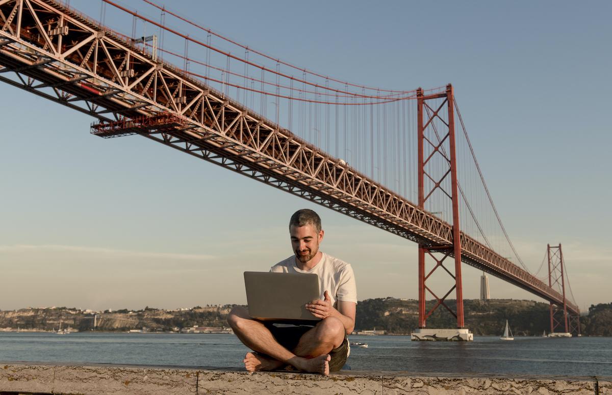 Человек с ноутбуком на мосту 25 апреля в Лиссабоне, Португалия