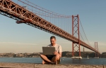 Man using laptop at 25th of April Bridge in Lisbon, Portugal