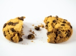 A homemade chocolate cookie with a bite and crumbs on a white background