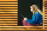 Teenage girl in mask sitting in window of modern house