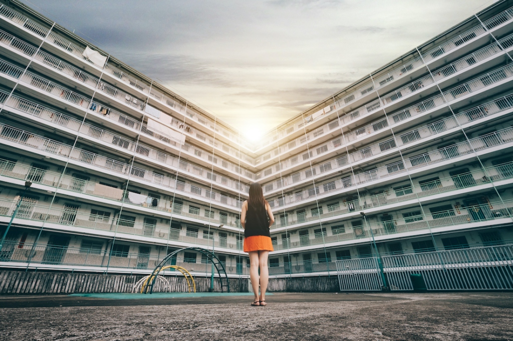 The rear view of woman standing against old apartment building, looking towards the shining sun.